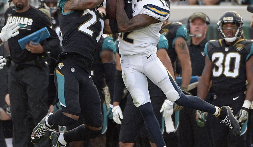 Jacksonville Jaguars cornerback A.J. Bouye , left, intercepts a pass intended for Los Angeles Chargers wide receiver Travis Benjamin during the second half of an NFL football game, Sunday, Nov. 12, 2017, in Jacksonville, Fla. Jacksonville won 20-17 in overtime. (AP Photo/Phelan M. Ebenhack)