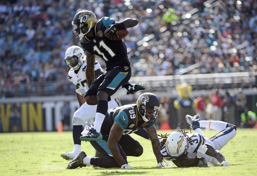 Jacksonville Jaguars wide receiver Marqise Lee (11) leaps over Los Angeles Chargers safety Jahleel Addae (37) after a reception during the first half of an NFL football game, Sunday, Nov. 12, 2017, in Jacksonville, Fla. (AP Photo/Phelan M. Ebenhack)