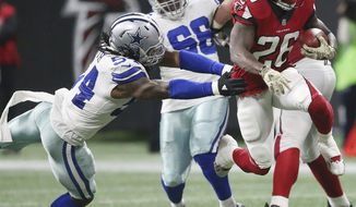 Atlanta Falcons running back Tevin Coleman (26) runs by Dallas Cowboys outside linebacker Jaylon Smith (54) during the second half of an NFL football game, Sunday, Nov. 12, 2017, in Atlanta. (AP Photo/John Bazemore)