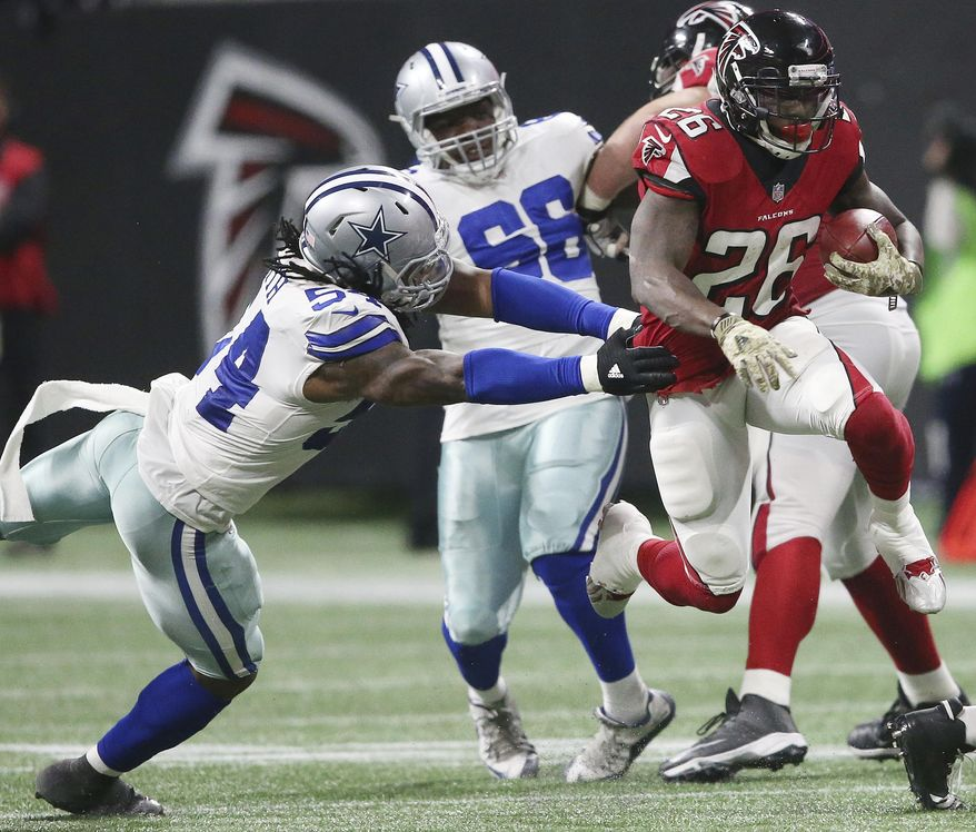 Atlanta Falcons running back Tevin Coleman (26) runs by Dallas Cowboys outside linebacker Jaylon Smith (54) during the second half of an NFL football game, Sunday, Nov. 12, 2017, in Atlanta. (AP Photo/John Bazemore)