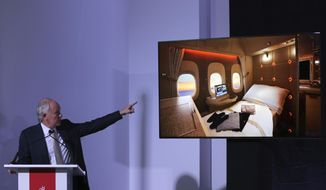 "Emirates Airline President Tim Clark points out the image of new, state-of-the-art, first class private suites, during a press conference at the opening day of the Dubai Air Show, United Arab Emirates, Sunday, Nov. 12, 2017. In an industry first, passenger suites in the middle aisle without windows will be fitted with ""virtual windows"" relaying the sky outside via fiber optic cameras on the plane. (AP Photo/Kamran Jebreili)"