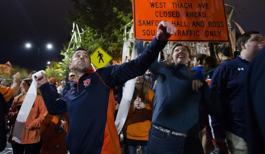 Matt McDonald and Elizabeth Pflug throw toilet paper at a tree near Toomer's Corner after the NCAA college football game between Auburn and Georgia on Saturday, Nov. 11, 2017, in Auburn, Ala. Auburn defeated Georgia 40-17. (Albert Cesare/The Montgomery Advertiser via AP)