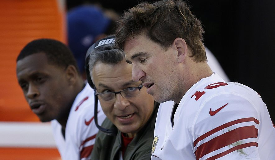 New York Giants quarterback Eli Manning, right, sits on the sideline with Geno Smith, left, and a coach during the second half of an NFL football game against the San Francisco 49ers in Santa Clara, Calif., Sunday, Nov. 12, 2017. (AP Photo/Ben Margot) **FILE**