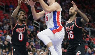 Detroit Pistons guard Luke Kennard (5) goes to the basket against Miami Heat forwards Josh Richardson (0) and James Johnson (16) during the second half of an NBA basketball game Sunday, Nov. 12, 2017, in Detroit. Kenner scored 14 points in the Pistons 112-103 win. (AP Photo/Duane Burleson)
