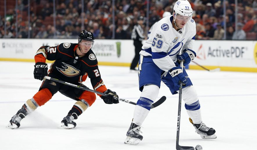 Tampa Bay Lightning defenseman Jake Dotchin (59) controls the puck ahead of Anaheim Ducks center Dennis Rasmussen (22) in the second period of an NHL hockey game in Anaheim, Calif., Sunday, Nov. 12, 2017. (AP Photo/Christine Cotter)