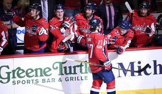 Washington Capitals right wing T.J. Oshie (77) celebrates his goal with the bench in a shootout of an NHL hockey game against the Edmonton Oilers, Sunday, Nov. 12, 2017, in Washington. The Capitals won 2-1 in a shootout. (AP Photo/Nick Wass)