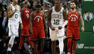 Boston Celtics' Terry Rozier (12) and Jayson Tatum (0) celebrate at the buzzer as Toronto Raptors' Kyle Lowry (7) and Fred VanVleet walk off the court after an NBA basketball game in Boston, Sunday, Nov. 12, 2017. (AP Photo/Winslow Townson)