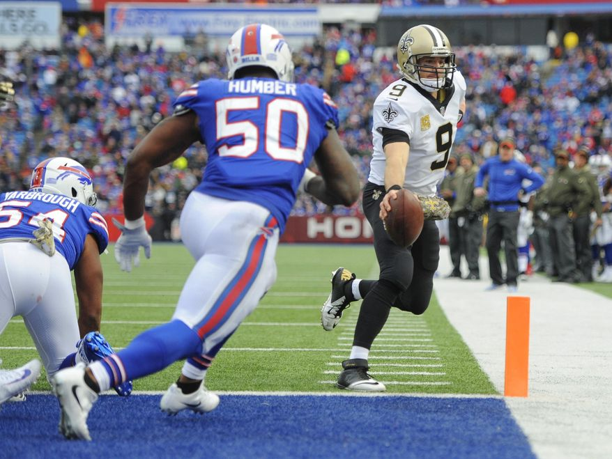 New Orleans Saints quarterback Drew Brees (9) rushes for a touchdown as Buffalo Bills' Ramon Humber (50) closes in during the second half of an NFL football game Sunday, Nov. 12, 2017, in Orchard Park, N.Y. (AP Photo/Adrian Kraus)