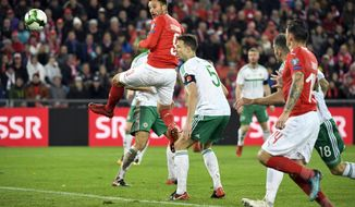 Switzerland's forward Haris Seferovic, in air fights for the ball with Northern Ireland's defender Jonny Evans, during the World Cup play-offs second leg soccer match between Switzerland and Northern Ireland at the St. Jakob-Park stadium in Basel, Switzerland, Sunday, Nov. 12, 2017. (Georgios Kefalas/Keystone via AP)