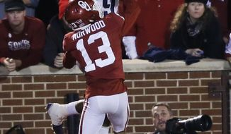 TCU wide receiver John Diarse (9) reaches for the ball but can't hold on as Oklahoma cornerback Tre Norwood (13) breaks up the play in the second half of an NCAA college football game in Norman, Okla., Saturday, Nov. 11, 2017. Oklahoma won 38-20. (AP Photo/Sue Ogrocki)