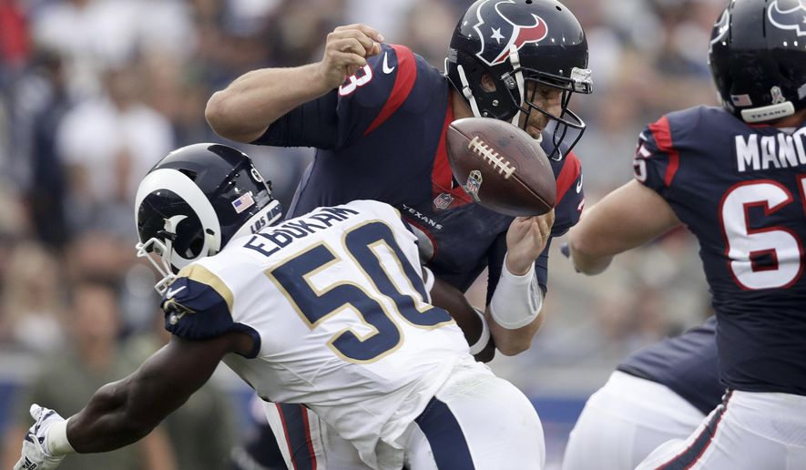 Los Angeles Rams linebacker Samson Ebukam, left, forces a fumble by Houston Texans quarterback Tom Savage during the second half of an NFL football game, Sunday, Nov. 12, 2017, in Los Angeles. (AP Photo/Jae C. Hong)