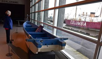 In this Nov. 2, 2017, photo, Carolyn Stock of Salem, Ore., looks at a display at the Columbia River Maritime Museum in Astoria, Ore., of a boat that washed ashore near Cape Disappointment as a result of the 2011 tsunami in Japan. The boat was donated to the museum after drifting across the Pacific Ocean and now serves as a reminder of the area's past with earthquakes and tsunamis. (Colin Murphey /Daily Astorian via AP)