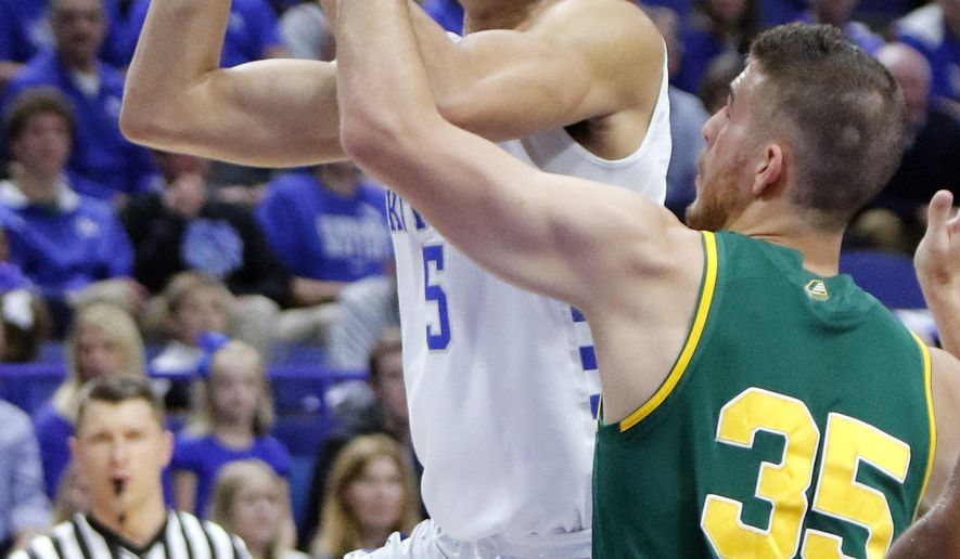 Kentucky's Kevin Knox, left, shoots around the defense of Vermont's Payton Henson (35) during the first half of an NCAA college basketball game, Sunday, Nov. 12, 2017, in Lexington, Ky. (AP Photo/James Crisp)