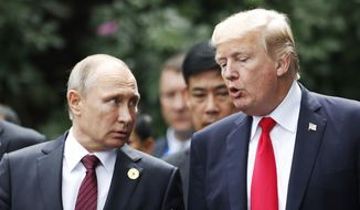 U.S. President Donald Trump and Russia's President Vladimir Putin talk during the family photo session at the APEC Summit in Danang, Vietnam, Saturday, Nov. 11, 2017. (Jorge Silva/Pool Photo via AP) ** FILE **