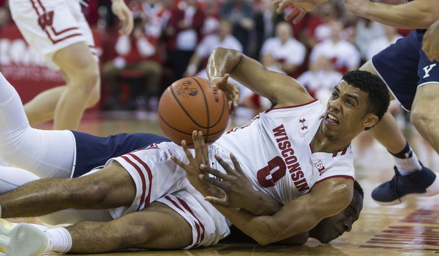 Wisconsin's D'Mitrik Trice (0) and Yale's Miye Oni, bottom, battle for a loose ball during the first half of an NCAA college basketball game Sunday, Nov. 12, 2017, in Madison, Wis. (AP Photo/Andy Manis)