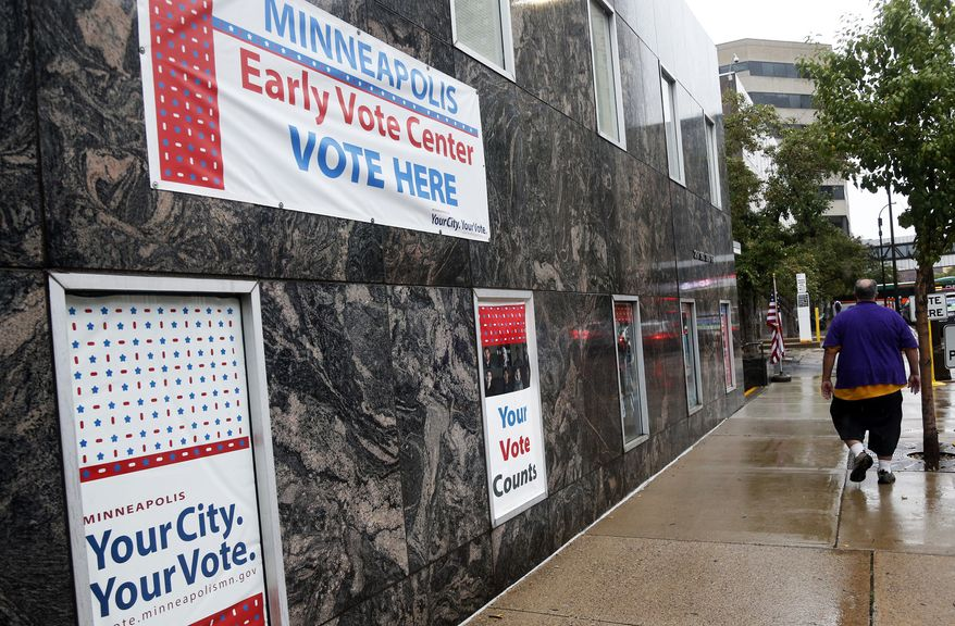 Signs on a building advertise early voting Friday, Sept. 23, 2016, in Minneapolis. Election Day is more than a month away but the voting was already underway Friday, as Minnesota kicked off its first presidential cycle where all voters across the state can cast their ballots early. (AP Photo/Jim Mone)