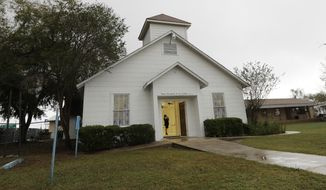 A visitor stands in the doorway of a memorial for the victims of the shooting at Sutherland Springs Baptist Church includes 26 white chairs, each painted with a cross and and rose, placed in the sanctuary, Sunday, Nov. 12, 2017, in Sutherland Springs, Texas. A man opened fire inside the church in the small South Texas community last week, killing more than two dozen. (AP Photo/Eric Gay)