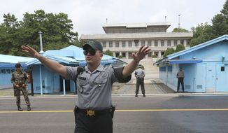 In this July 19, 2017, file photo, a South Korea army soldier gestures at the border villages of Panmunjom in Paju, South Korea. North Korean soldiers shot at and wounded a fellow soldier who was crossing a border village in an attempt to defect to South Korea on Monday, Nov. 13, 2017, the South's military said. (AP Photo/Ahn Young-joon, File)