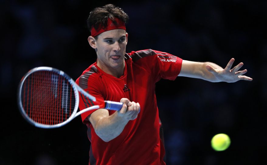 Dominic Thiem of Austria returns the ball to Grigor Dimitrov of Bulgaria during their singles tennis match at the ATP World Finals at the O2 Arena in London, Monday, Nov. 13, 2017. (AP Photo/Kirsty Wigglesworth)