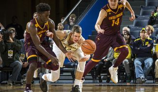 Michigan forward Moritz Wagner, center, contest for a loose ball with Central Michigan guard Gavin Peppers, left, and forward David DiLeo, right, in the first half of an NCAA college basketball game at Crisler Center in Ann Arbor, Mich., Monday, Nov. 13, 2017. (AP Photo/Tony Ding)