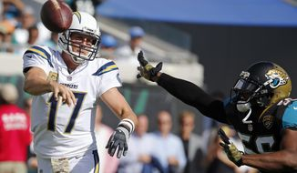 Los Angeles Chargers quarterback Philip Rivers (17) throws a pass as he is pressured by Jacksonville Jaguars defensive end Dante Fowler Jr., during the first half of an NFL football game, Sunday, Nov. 12, 2017, in Jacksonville, Fla. (AP Photo/Stephen B. Morton)