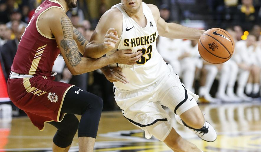Wichita State's Conner Frankamp, right, drives to the basket against College of Charleston's Grant Riller, left, during the first half of an NCAA college basketball game Monday, Nov. 13, 2017, in Wichita, Kan. (Fernando Salazar/The Wichita Eagle via AP)