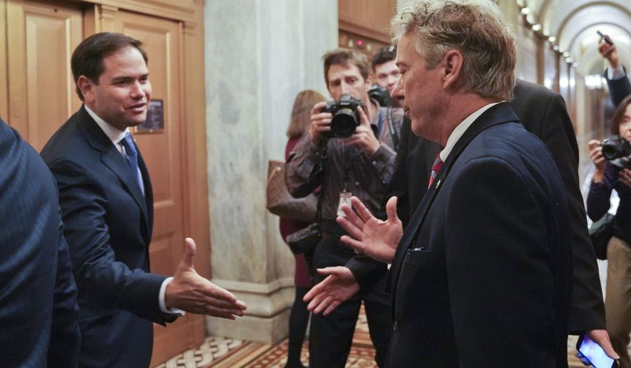Sen. Marco Rubio, R-Fla., left, extends his hand to welcome back Sen. Rand Paul, R-Ky., right, on Capitol Hill in Washington, Monday, Nov. 13, 2017. Paul declined to shake hands because of his injury after being attacked by his neighbor while he was mowing his lawn, according to authorities. (AP Photo/Pablo Martinez Monsivais)