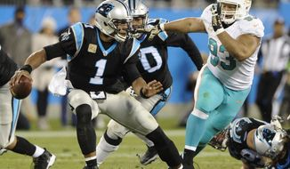 Carolina Panthers' Cam Newton (1) scrambles under pressure from Miami Dolphins' Ndamukong Suh (93) in the first half of an NFL football game in Charlotte, N.C., Monday, Nov. 13, 2017. (AP Photo/Mike McCarn)