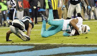 Miami Dolphins' T.J. McDonald (22) tries to intercept a pass intended for Carolina Panthers' Russell Shepard (19) in the first half of an NFL football game in Charlotte, N.C., Monday, Nov. 13, 2017. The pass was ruled incomplete after a review. (AP Photo/Mike McCarn)