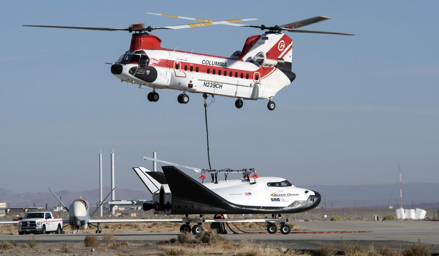This Nov. 11, 2017 photo provided by Sierra Nevada Corporation shows the Dream Chaser spacecraft being lifted by a helicopter prior to a test flight at Edwards Air Force Base, Calif. The Sierra Nevada Corp. says its Dream Chaser had a successful free-flight drop test in the Mojave Desert on Saturday, Nov. 11, 2017. (Ken Ulbrich/NASA via AP)