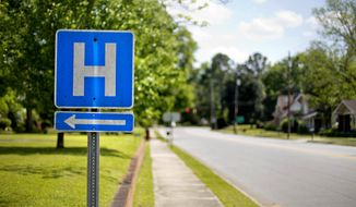 FILE - In this April 25, 2014, file photo, a sign points the way to a hospital in Georgia. A study shows that Medicare patients with common illnesses who were treated by their own familiar primary care doctors were slightly more likely to survive after being sent home than those treated by hospitalists, internists who don't provide care outside of hospitals. (AP Photo/David Goldman, File)