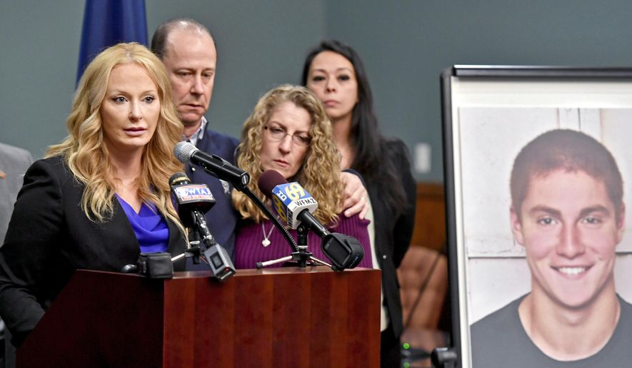 In this May 5, 2017, file photo, Centre County, Pa., District Attorney Stacy Parks Miller, left, announces findings an investigation into the death of Penn State University fraternity pledge Tim Piazza, seen in photo at right, as his parents, Jim and Evelyn Piazza, second and third from left, stand nearby during a news conference in Bellefonte, Pa. Parks Miller announced Monday, Nov. 13, 2017, that more charges have been filed against fraternity brothers after investigators recovered deleted surveillance video footage recorded before the Feb. 4, 2017, death of Piazza, of Lebanon, N.J., after a night of heavy drinking. (Abby Drey/Centre Daily Times via AP, File)/Centre Daily Times via AP)