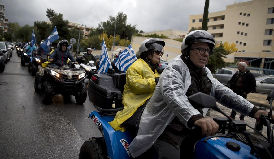 Protesters with Greek flags drive their all-terrain vehicles, ATV, during a rally outside the Greek Transport Ministry in Athens, Monday, Nov. 13, 2017. Hundreds of four-wheel motorbike owners, most from Greek holiday resorts, have blocked traffic outside the country's Transport Ministry to protest a proposed vehicle ban. (AP Photo/Petros Giannakouris)