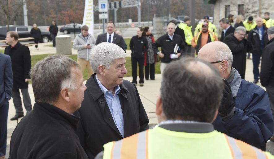 "Michigan Gov. Rick Snyder, second from left, talks with a group ahead a celebration of the new Michigan Department Of Transportation's ""flex route"" on U.S. 23 at the Northfield Church Rest Area 814 on Monday, Nov. 13, 2017. (Melanie Maxwell/The Ann Arbor News via AP)"