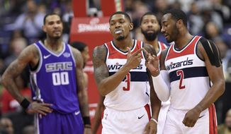 Washington Wizards guards John Wall (2) and Bradley Beal (3) react after Beal was fouled during the first half of an NBA basketball game against the Sacramento Kings, Monday, Nov. 13, 2017, in Washington. At left is Kings center Willie Cauley-Stein. (AP Photo/Nick Wass)