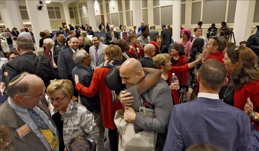 In this Tuesday Feb. 14, 2017 photo, Duval Schools Superintendent Nikolai Vitti, center, is hugged after the Jacksonville City Council voted 12-6 to support the Human Rights Ordinance (HRO) in Jacksonville, Fla. At left are Rabbi Rick Shapiro, the Interim Senior Rabbi at Congregation Ahavath Chesed, and Nancy Broner, Executive Director of OneJax. At the U.S. Capitol, and in most statehouses nationwide, supporters of LGBT rights are unable to make major gains these days. Instead, they're notching victories in scores of cities and towns that have acted on their own in Republican-governed states. (Bob Mack/Florida Times-Union via AP)