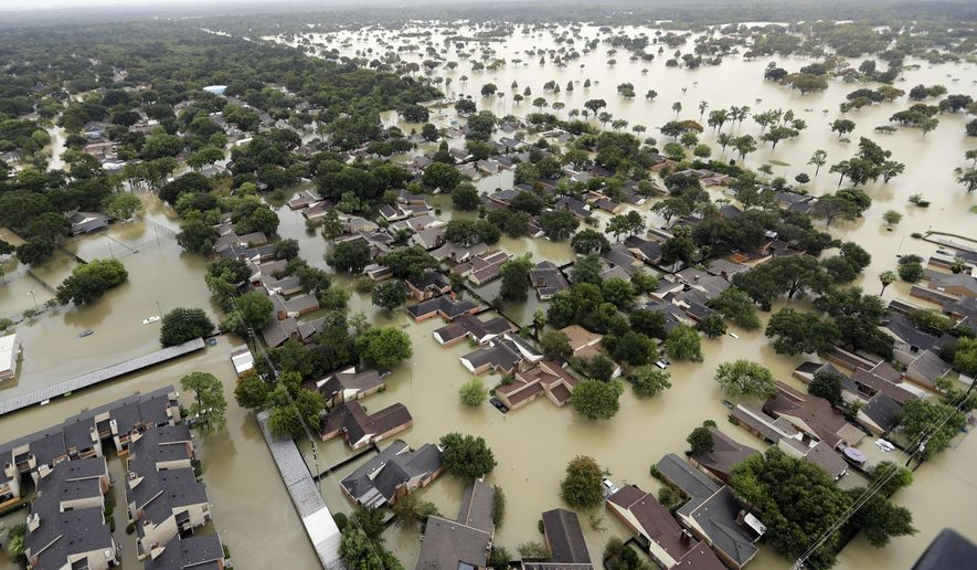 FILE - In this Tuesday, Aug. 29, 2017 file photo, water from Addicks Reservoir flows into neighborhoods as floodwaters from Tropical Storm Harvey rise in Houston. The chances of a hurricane drenching Texas, like Harvey did, have soared six fold in just a quarter century with global warming and will likely triple once again before the end of the century, says a new study published Monday, Nov. 12, 2017, in the Proceedings of the National Academy of Sciences.  (AP Photo/David J. Phillip, File)