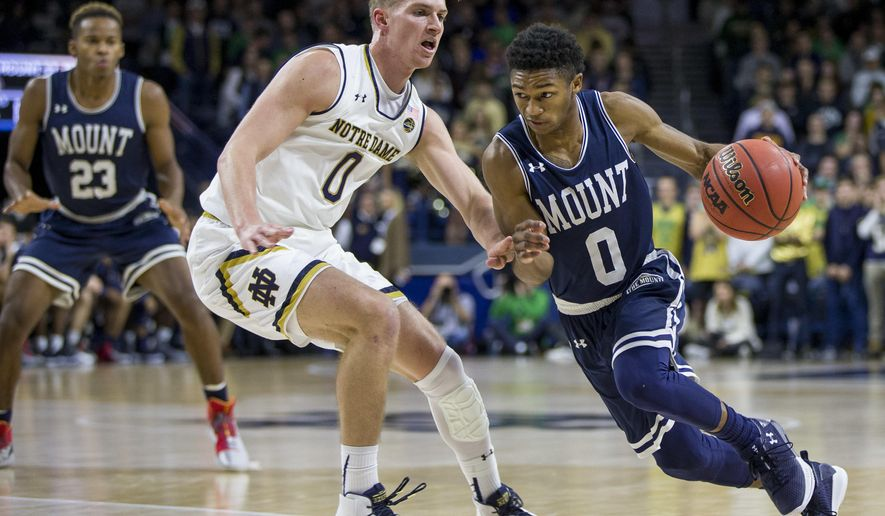 Mount St. Mary's Junior Robinson, right, drives against pressure from Notre Dame's Rex Pflueger during the first half of an NCAA college basketball game Monday, Nov. 13, 2017, in South Bend, Ind. (AP Photo/Robert Franklin)