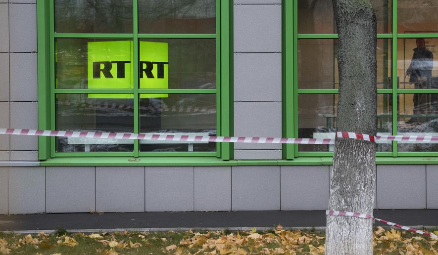 FILE - In this Oct. 27, 2017, file photo, Russian state-owned television station RT logo is seen at the window of the company's office in Moscow, Russia. Russian state-funded TV channel RT has registered with the Justice Department as a foreign agent after pressure from the U.S. government, documents released Nov. 13, 2017, show. (AP Photo/Pavel Golovkin, File)