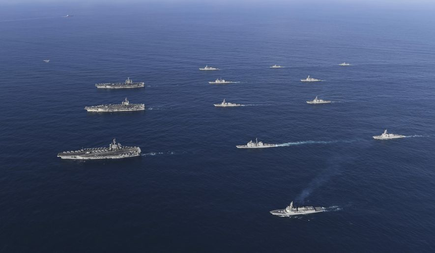 In this Nov. 12, 2017 photo provided by South Korea Defense Ministry, three U.S. aircraft carriers USS Nimitz, left top, USS Ronald Reagan, left center, and USS Theodore Roosevelt, left bottom, participate with other U.S. and South Korean navy ships during the joint naval exercises between the United States and South Korea in waters off South Korea's eastern coast in South Korea. The United States and South Korea on Saturday started joint naval exercises that will involve three U.S. aircraft carriers in what military officials describe as a clear warning to North Korea. (South Korea Defense Ministry via AP)