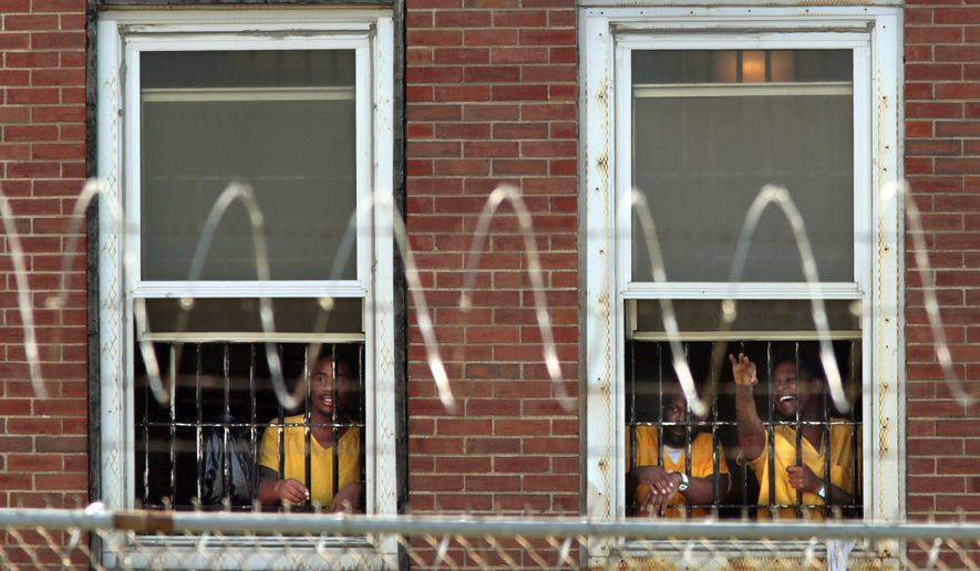 "In this July 24, 2017 photo, inmates watch the arrival of temporary air conditioning units from TempAir at the St. Louis Medium Security Institution, known better as the Workhouse. A lawsuit filed Monday, Nov. 13, alleges inmates at the medium-security jail in St. Louis live in ""inhumane conditions"" that include rodent feces in food, infestations of bugs and snakes, and unbearable overcrowding. (Robert Cohen/St. Louis Post-Dispatch via AP)"