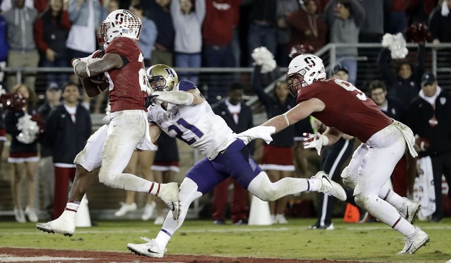Stanford running back Bryce Love, left, scores a touchdown past Washington defensive back Taylor Rapp (21) during the second half of an NCAA college football game Friday, Nov. 10, 2017, in Stanford, Calif. Stanford won 30-22. (AP Photo/Marcio Jose Sanchez)