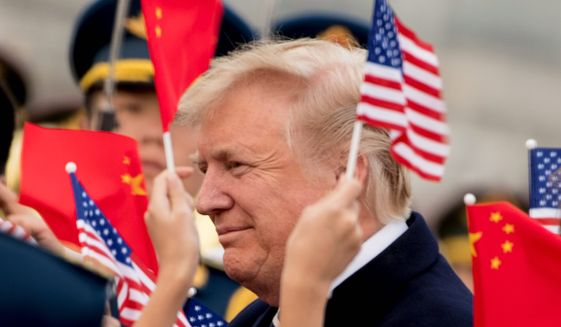 Children wave U.S. and Chinese flags as President Donald Trump arrives at Beijing Airport, Wednesday, Nov. 8, 2017, in Beijing, China. Trump is on a five country trip through Asia traveling to Japan, South Korea, China, Vietnam and the Philippines. (AP Photo/Andrew Harnik)