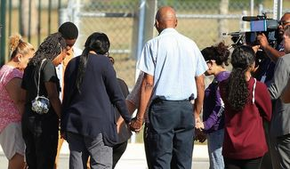 Parents prayed in front of Lake Minneola High School in Florida on Tuesday after a student shot and killed himself there. Researchers have found a disturbingly strong correlation between heavy social media use and teenage suicide, along with other mental health issues. (Associated Press)