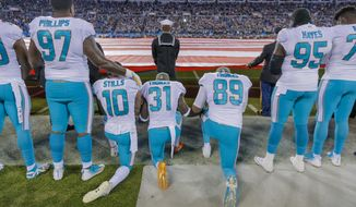 Miami Dolphins' Jordan Phillips (97) stands during the national anthem, but shows support for the protest as he puts an arm on the shoulder of kneeling teammate, Kenny Stills (10), Michael Thomas (31) and Julius Thomas (89) before an NFL football game against the Carolina Panthers in Charlotte, N.C., Monday, Nov. 13, 2017. The Panthers won 45-21. (AP Photo/Bob Leverone)