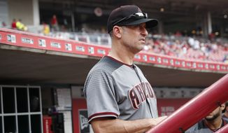 FILE - In this July 20, 2017, file photo, Arizona Diamondbacks manager Torey Lovullo works in the dugout during the seventh inning of the team's baseball game against the Cincinnati Reds in Cincinnati. Luvullo won the National League Manager of the Year Award on Tuesday, Nov. 14, 2017. In his first full season as a big league skipper, Arizona reached the playoffs a year after going 69-93. (AP Photo/John Minchillo, File) **FILE**