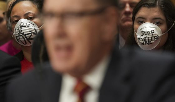 Anti-nuclear war demonstrators sits wearing a mask as they listen to General C. Robert Kehler, center, USAF (Ret.) former Commander United States Strategic Command, testify during a Senate Foreign Relations Committee hearing on North Korea on Capitol Hill in Washington, Tuesday, Nov. 14, 2017. (AP Photo/Pablo Martinez Monsivais)