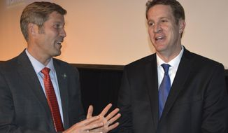 In this Wednesday, Nov. 8, 2017, photo New Mexico State Auditor Tim Keller, left, and Albuquerque City Councilor Dan Lewis speak after participating in a Albuquerque mayoral forum at the South Broadway Cultural Center in Albuquerque, N.M. Voters will decide Tuesday, Nov. 14, 2017 between Keller and Lewis in a race that largely has focused on rising crime in Albuquerque and the city's struggling economy. (AP Photo/Russell Contreras)