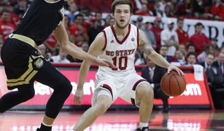 N.C. State's Braxton Beverly (10) dribbles around Bryant's Ryan Layman (5) during the first half of an NCAA college basketball game in Raleigh, N.C., Tuesday, Nov. 14, 2017. (Ethan Hyman/The News & Observer via AP)
