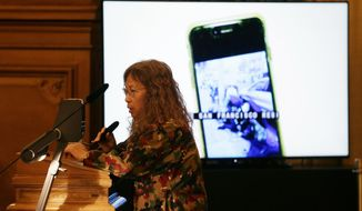 Sonie Ng expresses her concern on the location of recreational cannabis stores while an image of drug usage from her phone is displayed during a Board of Supervisors meeting at City Hall, Monday, Nov. 13, 2017, in San Francisco. The path toward legalizing recreational cannabis in weed-friendly San Francisco has taken a surprisingly contentious turn as critics, who are largely older Chinese American immigrants with clout, have lobbied against placing retail stores too close to children. (AP Photo/Eric Risberg)